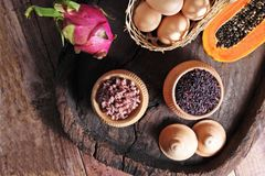 Food scenery on wooden background. Basket of eggs, rice pot, Dragon fruit and papaya on wooden tray Royalty Free Stock Photo