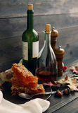 Food seasoning and spices and other cooking-condiments. Wine in a bottle, balsamic vinegar, pepper mill of wood and honey in honeycombs on a plate on a wooden Royalty Free Stock Image