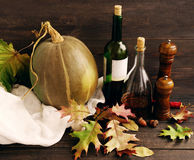 Food seasoning and spices and other cooking-condiments. Wine in a bottle, balsamic vinegar, pepper mill of wood and pumpkin on a wooden surface with autumn Stock Photos