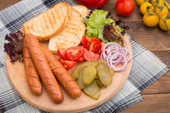 Food set for hot dog, sausage, canned cucumbers, lettuce leaves, tomatoes, onions, croutons on the wooden background Royalty Free Stock Photography