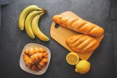 Bananas, lemons, one cut, loaves of white bread on the board and four croissants on a silver platter on a dark background. royalty free stock photo