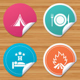 Food, sleep, camping tent and fire signs. Round stickers or website banners. Food, sleep, camping tent and fire icons. Knife, fork and dish. Hotel or bed and Royalty Free Stock Image