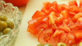 Food. slices of tomatos, and green olive vegetable on white cutting board stock footage