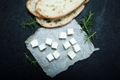 Food for a small snack, traditional feta cheese, bread and rosemary on a black background stock photos