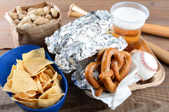 Food and Souvenirs at a Baseball Game. Closeup of a tray of food and souvenirs that one would find at a baseball game. Items include, hot dogs wrapped in foil Stock Image