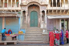 NAWALGARH, RAJASTHAN, INDIA - DECEMBER 26, 2017: Food stalls in front of a restored Haveli with colorfully dressed people. Food stalls in front of a restored Royalty Free Stock Images