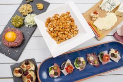 Food starters - roasted peanuts, tartare steak, open sandwiches and cheese Stock Photo