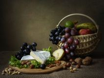 Still life with basket of beautiful orchids on the table. Food still life with mixed cheeses and ripe fruits in vintage style stock photo