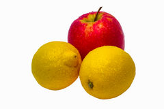 Two yellow wet lemons and one red apple isolated Stock Images