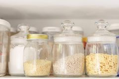 Food stocks on a white kitchen shelf glass jars with cereal, pasta, corn flakes stock photo