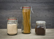 Food storage. Food ingredients in glass jars, on wood background. Stock Photos