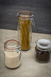 Food storage. Food ingredients in glass jars, on wood background. Royalty Free Stock Images