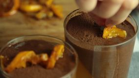 Food styling chocolate mousse with orange jelly dessert. On table in the kitchen closeup stock video footage