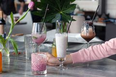 Food stylist and photographer decorate, preparing to shoot various cocktails, milkshakes, smoothies, flower tulips in vase on. Table. Concept professional royalty free stock images