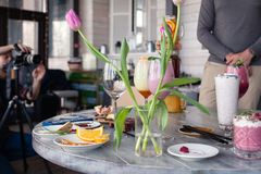 Food stylist and photographer decorate, preparing to shoot various cocktails, milkshakes, smoothies, flower tulips vase on table. Food stylist and photographer royalty free stock image