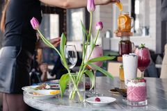 Food stylist and photographer decorate, preparing to shoot various cocktails, milkshakes, smoothies, flower tulips vase on table. Food stylist and photographer stock images