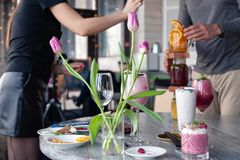 Food stylist and photographer decorate, preparing to shoot various cocktails, milkshakes, smoothies, flower tulips vase on table. Food stylist and photographer royalty free stock images