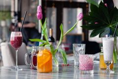 Food stylist and photographer decorate, preparing to shoot various cocktails, milkshakes, smoothies, flower tulips in vase on. Table. Concept professional royalty free stock photos