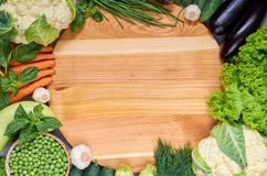Food summer background with copy space for text. Fresh organic vegetables around wooden board. Raw ingredients for salad, soup. Food summer background with copy Royalty Free Stock Images
