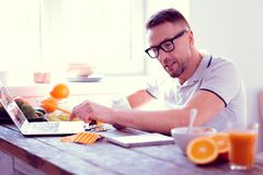 Bearded man leading healthy lifestyle studying info about food supplements. Food supplements. Bearded handsome athletic man leading healthy lifestyle studying royalty free stock photography