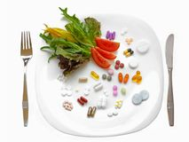 Food supplements vs healthy diet. Nutritional supplement vs healthy eating: mixed pills, tablets and capsules nicely laid on a white plate alongside some fresh Royalty Free Stock Photos