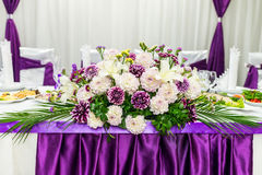 Food table decorated with flowers. Food table decorated with purple and white beautifu flowers for wedding Royalty Free Stock Photo