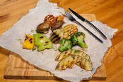 Food on the table. Fried vegetables with mushrooms on paper Stock Photos