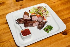 Food on the table. Meat cut from sausages with vegetable salad and sauce Stock Photos