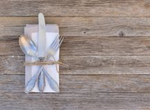 Place setting with elegant cutlery and napkin on wooden table background. Food table place setting with silverware and napkin and on wooden table, top view royalty free stock photography