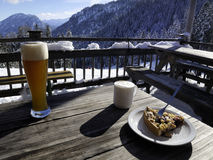 Food on table at ski lodge. Wheat beer, coffee and cake on wood picnic table at a Bavarian ski resort lodge in winter Stock Photography