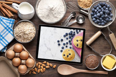 Food Tablet Baking Cooking. A computer tablet surround by food ingredients and utensils on a rustic wood background with blueberry muffins on the screen and room Royalty Free Stock Images