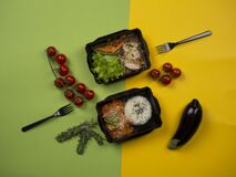 Food in takeaway box: rice with fish in sweet and sour sauce, chicken with buckwheat, vegetables and green salad.