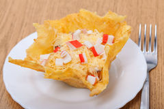 Food - tasty course. Food - plate with snack - cheese basket with crabbing salad on a table Royalty Free Stock Images