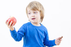 Food Temptation. A perplexed blond boy fighting with food temptation Stock Photography