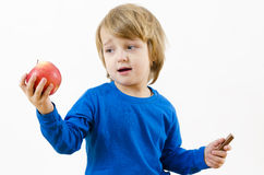 Food Temptation. A perplexed blond boy fighting with food temptation royalty free stock photography