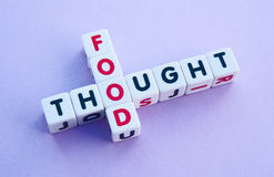 Food for thought. Text ' food ' and ' thought ' in uppercase letters inscribed on small white cubes arranged crossword style  with common letter ' o ', purple Stock Photos