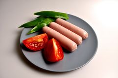Food - three sausages on a gray plate. With vegetables stock photos