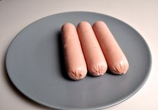 Food - three sausages on a gray plate. With vegetables royalty free stock photography