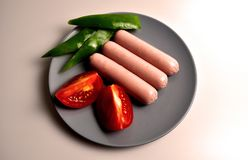 Food - three sausages on a gray plate. With vegetables stock image