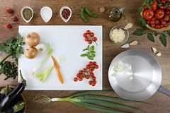 Food top view, cut onion in a frying pan on wooden work top. With white cutting board, ingredients and vegetables royalty free stock image