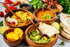 Food traditional Indian cuisine. Dal, palak paneer, curry, rice, chapati, chutney in wooden bowls on white background