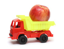 Food transportation concept - toy lorry with apple Stock Photos