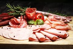 Food tray with delicious salami, pieces of sliced ham, sausage and salad. Meat platter selection. Food tray with delicious salami, pieces of sliced ham, sausage stock images