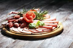 Food tray with delicious salami, pieces of sliced ham, sausage and salad. Meat platter selection. Food tray with delicious salami, pieces of sliced ham, sausage royalty free stock photography