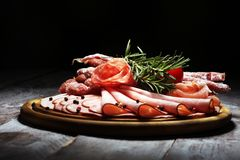 Food tray with delicious salami, pieces of sliced ham, sausage and salad. Meat platter selection. Food tray with delicious salami, pieces of sliced ham, sausage stock image
