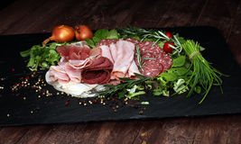 Food tray with delicious salami, pieces of sliced ham, sausage, tomatoes, salad and vegetable - Meat platter with selection. Food tray with delicious salami stock photos