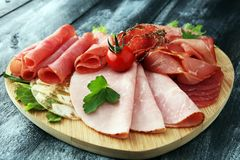 Food tray with delicious salami, pieces of sliced ham, sausage, tomatoes, salad and vegetable - Meat platter with selection. Food tray with delicious salami stock image