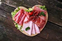 Food tray with delicious salami, pieces of sliced ham, sausage, tomatoes, salad and vegetable - Meat platter with selection. Food tray with delicious salami royalty free stock photography