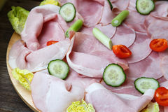Food tray with delicious salami, pieces of sliced ham Stock Images