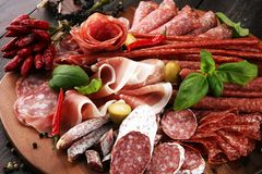 Food tray with delicious salami, pieces of sliced prosciutto crudo, sausage and basil. Meat platter with selection. Food tray with delicious salami, pieces of royalty free stock photography